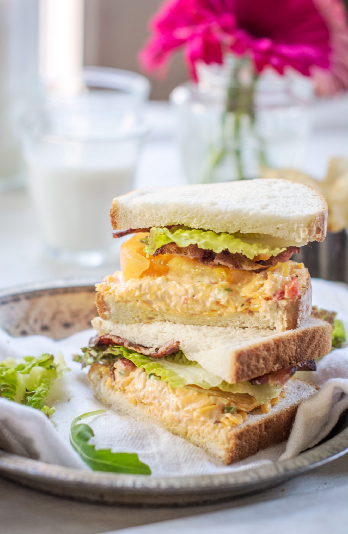 A stacked sandwich on Pepperidge Farm hearty white bread with pimiento cheese, bacon, lettuce and tomatoes.