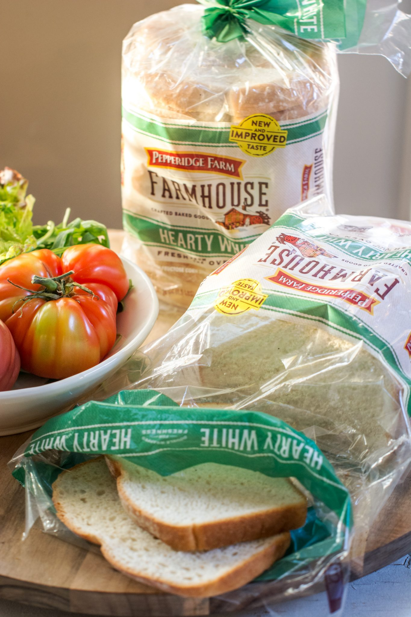 Pepperidge Farm hearty white bread in wrapping beside a bowl of tomatoes.