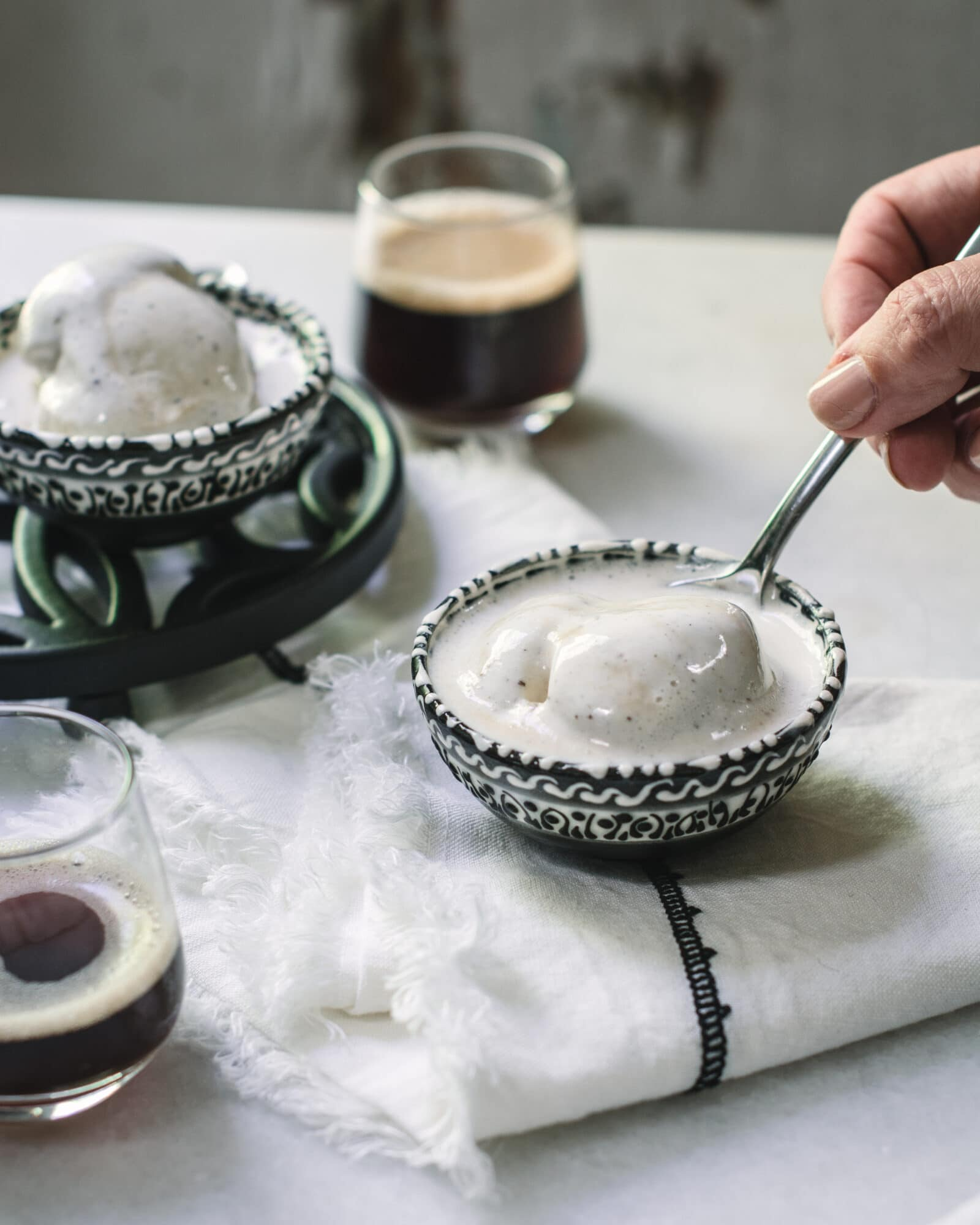 Serving affogato in bowls on white table with hand holding spoon