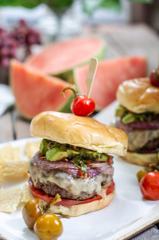 A chimichurri burger recipe with melted cheese, tomatoes, caramelized onions, avocado slices and cherry peppers