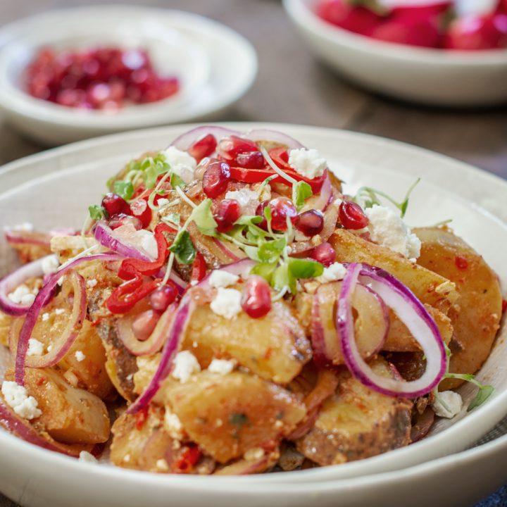 White bowl with Moroccan Potato Salad on wood table