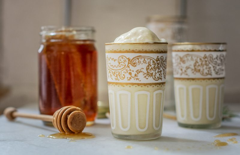 Rosemary infused Honey Ice Cream in decorative glasses beside a jar of honey