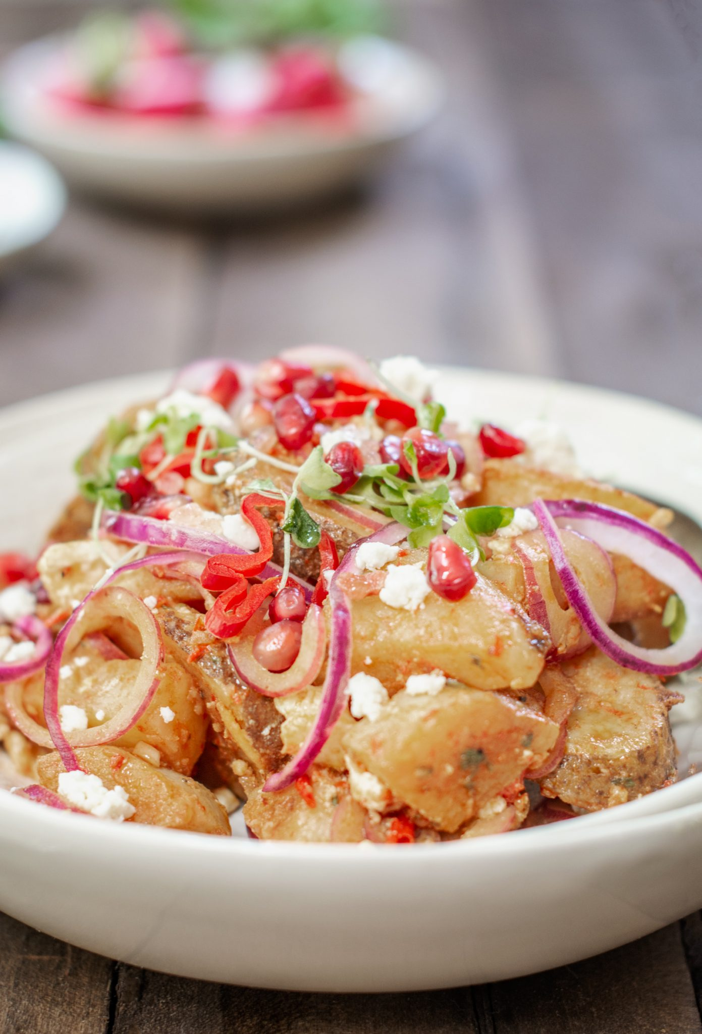 Bowl filled with Moroccan Potato Salad, pomegranate seeds and onions