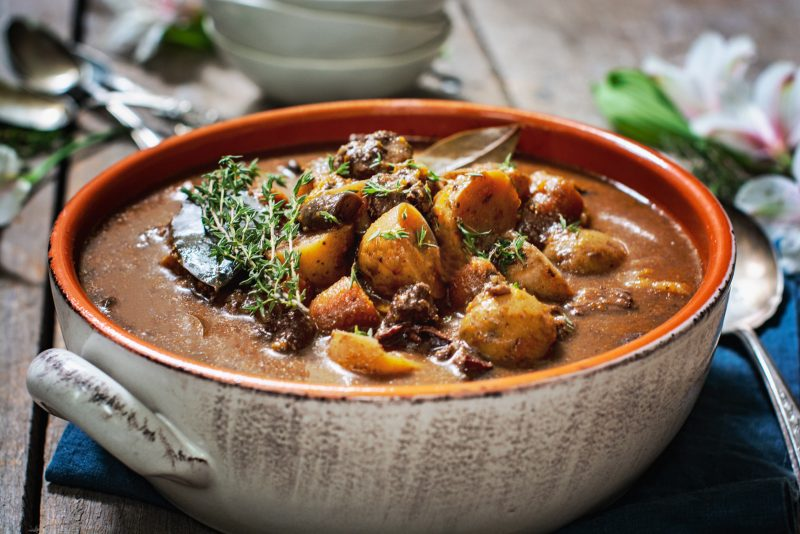 A cozy bowl of Beef Bourguignon, with spoons on brown wooden table.