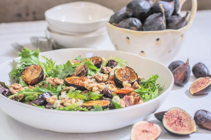 Ready to serve grilled fig salad in large white bowl.