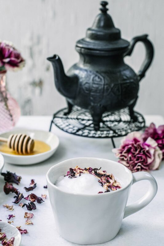 Hibiscus Flower Tea Latte with honey on white table