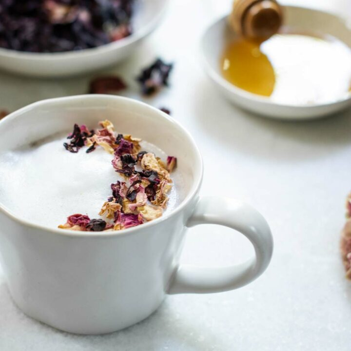 White table with frothy milky tea garnished with dried flowers