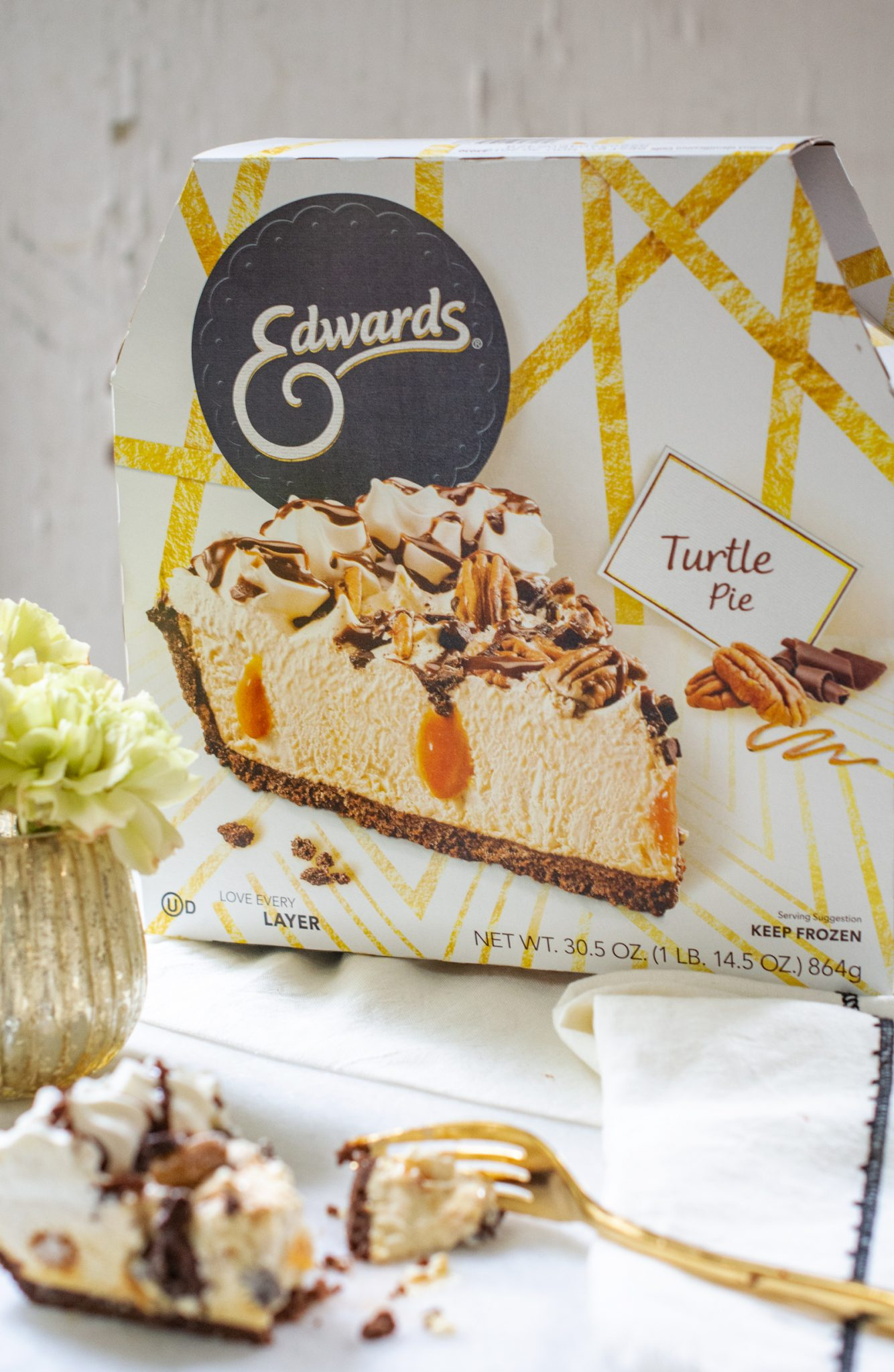 Edwards Desserts Turtle Pie package with slice of pie in foreground with gold fork