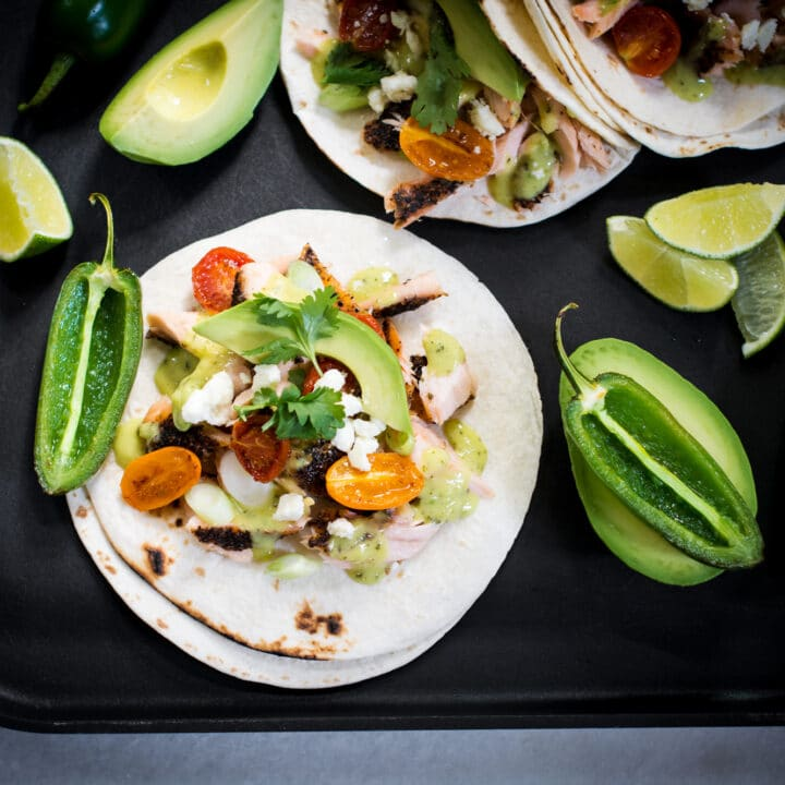 Fish tacos served with avocado, salsa, and jalapenos
