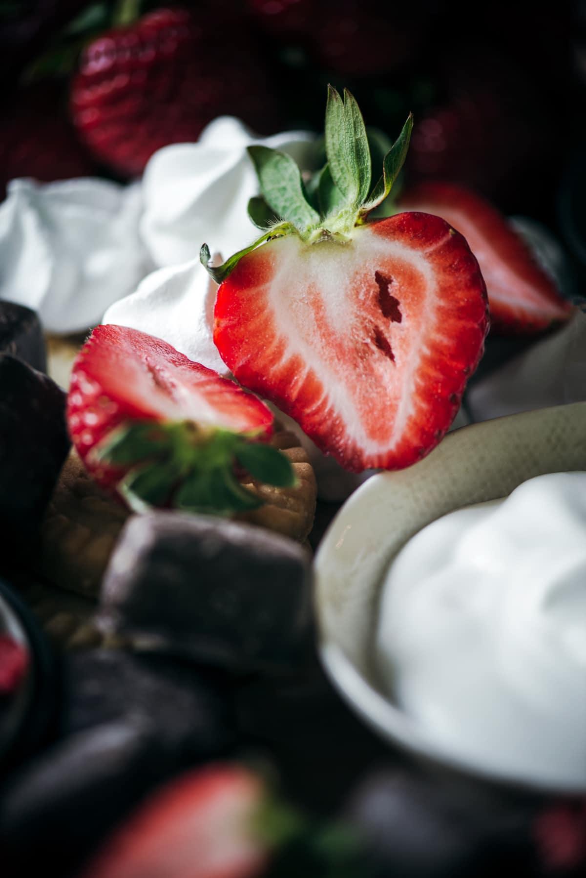 Halved fresh strawberries on dessert board