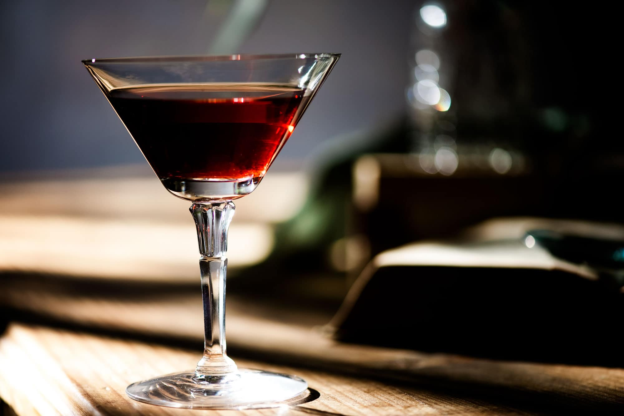 Martini glass with red drink sitting on a wood counter
