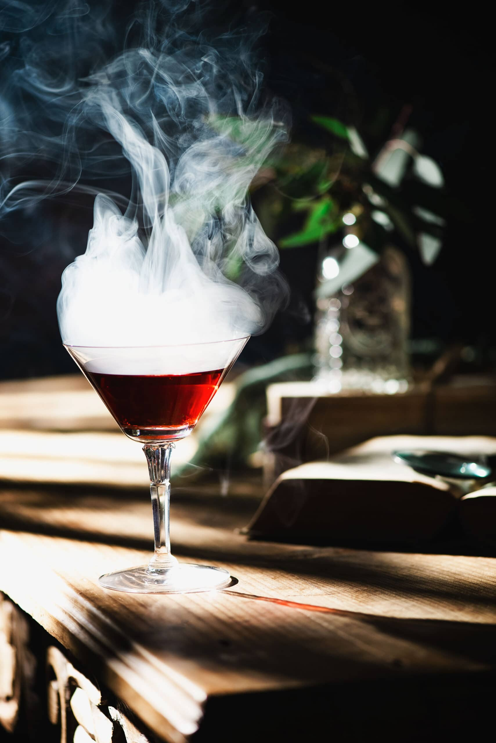 Martini glass with Washington apple cocktail and smoke on wooden table