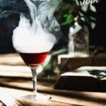 Drink in glass with smoke on wooden table